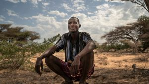 Kenialainen paimen William istuu puun alla