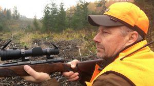 hirvenmetsästäjä passissa metsän laidalla aseen kanssa