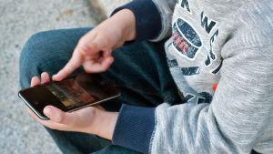 Lapsi kännykkä kädessään.