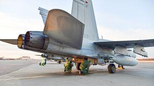 Lentotekniikan henkilöstö valmistelee ilmavoimien Hornetia tehtävälle koneen moottoreiden jo käydessä.