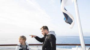Isä osoittaa, poika katsoo, taustalla meri.