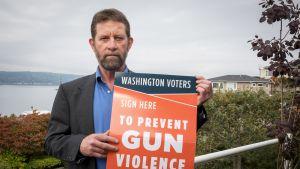 """Mies katsoo kameraan käsissään juliste, jossa lukee """"sign here to prevent gun violence""""."""