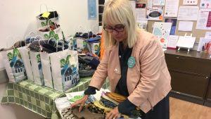 EHYT ry:n aluekoordinaattori Anne Mikkola lajittelee lahjoitettuja käsitöitä.