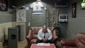 Yrittäjä -elokuvan pressikuva. Mies istuu olohuoneen pöydän ääressä.