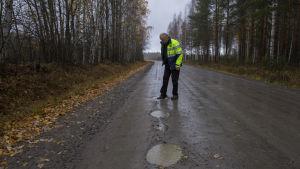 Rautalampilainen Pentti Raatikainen tutkii Saikarintien kuoppia.