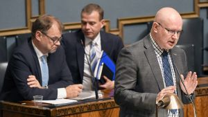 Työministeri Jari Lindström sekä taustalla pääministeri Juha Sipilä ja valtiovarainministeri Petteri Orpo eduskunnan täysistunnossa Helsingissä 16. lokakuuta