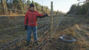 Tauno Kunnari tutkii radan varteen rakennettua aitaa Rovaniemen Muurolassa.