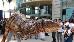 Luonnollisen kokoinen ja näköinen dinosaurusnukke, josta kuitenkin pilkistävät sitä liikuttelevan ihmisen jalat. Otus haistelee pelästynyttä pikkutyttöä, ympärillä hymyileviä ja valokuvaavia ihmisiä.