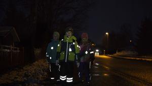 Heijastinta käyttäviä lapsia pimeällä kadulla.