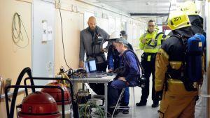Pelastushenkilöstöä ja tutkijoita terveyskeskuksen käytävällä.