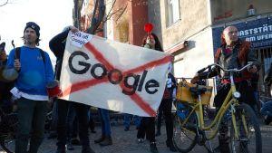 """Ihmiset pitelemässä kylttiä, jossa sanan """"Google"""" päällä on punaiset ruksit."""