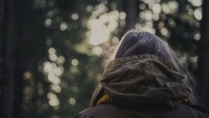 Nainen seisoo puuston edessä.