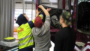 Oppilaat korjaavat kuorma-auton ovipaneelia.