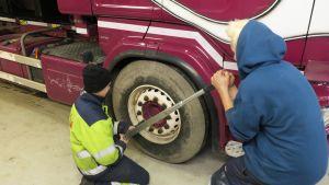 Oppilaat kiristävät kuorma-auton renkaan pultteja.