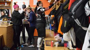 Nuori naiskiekkoilija joukkueen pukuhuoneessa pukemassa varusteita päälleen