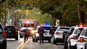 Hälytysajoneuvo ja poliiseja Pittsburghin kadulla.