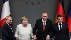 Venäjän presidentti Vladimir Putin, Saksan liittokansleri Angela Merkel, Turkin presidentti Recep Tayyip Erdogan ja Ranskan presidentti Emmanuel Macron pitävät toisiaan kädestä huippukokouksen tiedotustilaisuudessa.