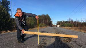Mies näyttää lankun ja mittanauhan avulla, millainen tievaurio hänen lähitiessään on.