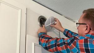 Isännöitsijä Sami Reinikka avaa asunnon poistoilmaventtiilin puhdistamista varten.