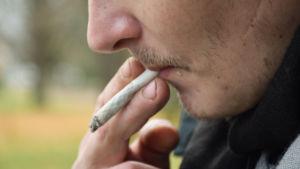 Mieshenkilö polttaa tupakkaa.