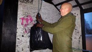 Soinin kunnanjohtaja Juha Viitasaari punnitsee muovijätettä MuoviSampo-keräyspisteellä.