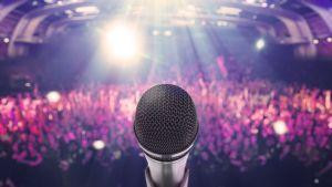 Mikrofoni ja yleisöä.