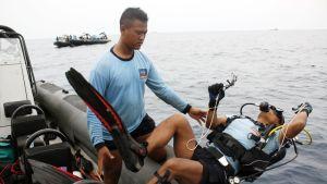 Indonesian laivaston sukeltajat etsivät turmakoneen osia.