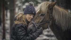 Nainen halaa hevosta