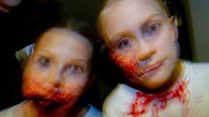 kaksi tyttöä halloween-kasvomaalauksissa.