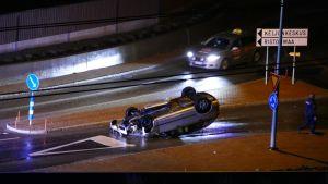 Henkilöauto on katollaan vastaantulevien kaistalla