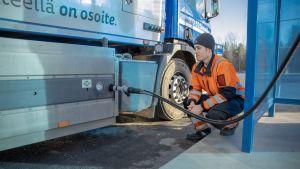 Kuljettaja tankkaa jäteautoon biokaasua.