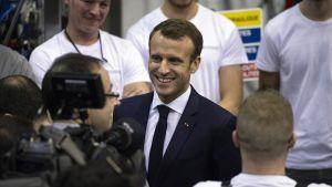 Kuvassa Emmanuel Macron ihmisten ympäröimänä.