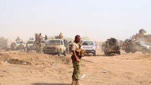 Mies seisoo hietikolla tuastalla autoja joiden päälä istuu ja seisoskelee ihmisiä aseiden kanssa.