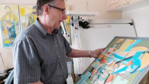 Raimo Lehtonen esittelee maalaustaan.