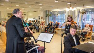 Klarinetisti Kimmo Leppälä, pianisti Ilkka Joronen ja alttoviulisti Heidi Ketola soittavat muistisairaille vanhuksille Sipoon Suvirinteen hoivakodissa.