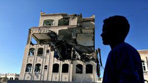 Jemeniläinen mies kävelee pommitetun talon ohi maaliskuussa 2018.