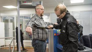 Vartija tarkastaa asiakasta oikeus- ja poliisitalon aulassa.