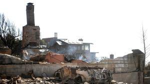 Etualalla palaneen talon jäänteet. Savupiippu jäänyt pystyyn. Sen takana oleva talo säilynyt vahingoittumattomana.