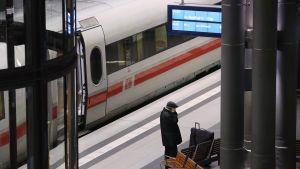 Mies puhuu kännykkään juna-aseman laiturilla Berliinissä.