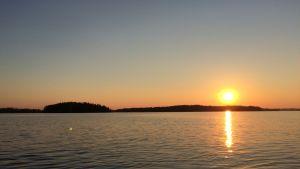 Kesäinen aurinkoinen illan järvimaisema.