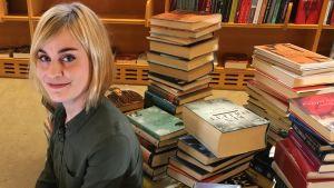 Nuori nainen istuu lattialla. Hänen takanaan on kirjoja pinoissa.