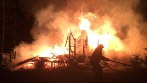 Palomies sammuttaa roihuavaa tulipaloa
