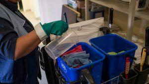 Nainen kaataa vettä siivouskärryssä oleviin mikrokuituliinoihin.