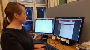 Reeta Knuuti katsoo tietokonetta.