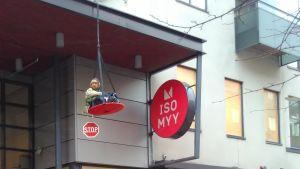 Mielenosoittaja roikkuu kauppakeskuksen sisäänkäynnin yläpuolella Joensuussa.