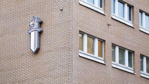 Poliisin logon Turun pääpoliisiaseman seinässä.