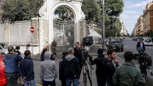 Suuren portin edustalla seisoo ihmisiä kameroiden kanssa.