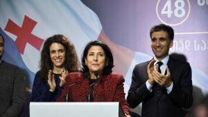 Nainen kahden mikrofonin edessä, hänen vierellään nainen ja mies tapauttavat.