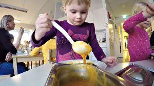 Tyttö annostelee keittoa lautaselleen päiväkodissa.