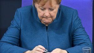 Angela Merkel käyttää puhelinta.